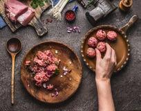 Mięsnych piłek robić Żeńska ręka stawia mięsną piłkę w smażyć nieckę Przygotowanie na kuchennym stole z mięsem, siły mięso, maszy Fotografia Stock