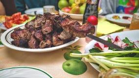 Mięso gotujący na grillu jest w talerzu na stole z warzywami fotografia royalty free