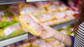 Mięso w sklepie spożywczym Kobieta wybiera upakowanego świeżego kurczaka mięso w supermarkecie obraz royalty free