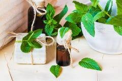Miętówka istotny olej w szklanej butelce na lekkim stole Używać w medycynie, kosmetykach i aromatherapy, Fotografia Royalty Free