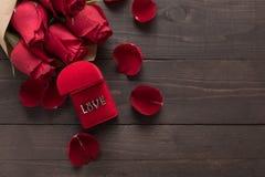 Miłość jest czerwone róże beside kwitnie na drewnianym tle Obraz Stock