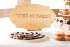 Miłość jest słodkim znakiem przy cukierku baru stołem Obraz Royalty Free