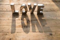 Miłość literująca out na drewnianym tle Obrazy Royalty Free