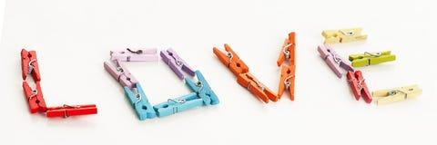 Miłość od małych kolorowych biurowych clothespins zdjęcia stock