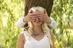 miłość pary Mężczyzna zakrywający oczy uśmiechnięta blondynki kobieta jego rękami w parku Zdjęcie Stock