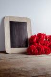 Miłość serca kształtują i opróżniają kredową deskę na drewnianym backg, czerwone róże Zdjęcie Stock