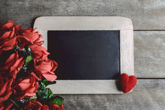 Miłość serca kształtują i opróżniają kredową deskę na drewnianym backg, czerwone róże Obraz Stock