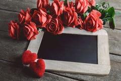 Miłość serca kształtują i opróżniają kredową deskę na drewnianym backg, czerwone róże Zdjęcie Royalty Free