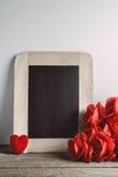 Miłość serca kształtują i opróżniają kredową deskę na drewnianym backg, czerwone róże Obrazy Stock