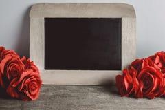 Miłość serca kształtują i opróżniają kredową deskę na drewnianym backg, czerwone róże Fotografia Royalty Free