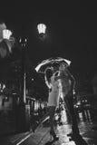 Miłość w podeszczowym, sylwetce całowanie para pod parasolem/ Zdjęcie Stock