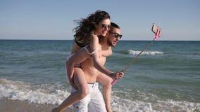 Miłości para robi Selfi fotografii na plaży, facet okrąża dziewczyny, pozytywni młodzi ludzie krótkopędu wideo od wakacyjnej podr zbiory