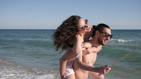 Miłości para robi selfie fotografii na plaży, facet okrąża dziewczyny, pozytywni młodzi ludzie krótkopędu wideo od wakacyjnej pod zbiory