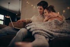 Miłości para w hygge domu z laptopem zdjęcie royalty free