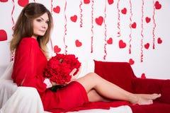 Miłości pojęcie - młoda wspaniała kobieta w czerwieni sukni obsiadaniu w deco obraz stock