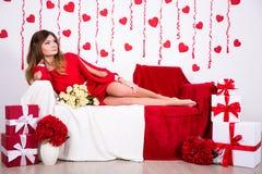 Miłości pojęcie - wspaniała kobieta w długim czerwieni sukni obsiadaniu w wystroju obraz stock