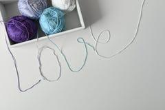 Miłości słowo od kolorowych bawełnianych nici od dziewiarskich przędz w białym pudełku z kopii przestrzenią pod nim na białym tle obrazy stock