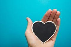 miłości siatki znaka wektor Czarny deskowy serce w kobiet rękach na błękitnym tle Obraz Stock