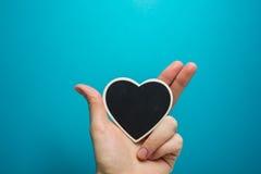miłości siatki znaka wektor Czarny deskowy serce w kobiet rękach na błękitnym tle Obraz Royalty Free