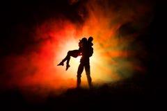 Miłości walentynki ` s dnia pojęcie Sillhouette słodcy potomstwa dobiera się w miłości stoi w polu i ściska na zmrok tonującym mg Zdjęcia Royalty Free