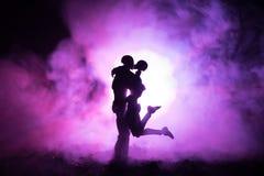 Miłości walentynki ` s dnia pojęcie Sillhouette słodcy potomstwa dobiera się w miłości stoi w polu i ściska na zmrok tonującym mg Obraz Royalty Free
