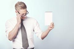 Miły biznesmen patrzeje pustego notatnika. obrazy royalty free