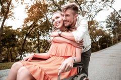 Miły mężczyzna ściska jego niepełnosprawnej dziewczyny i patrzeje szczęśliwy obraz stock