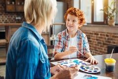 Miły mały malarz opowiada z babcią i ono uśmiecha się Zdjęcia Stock
