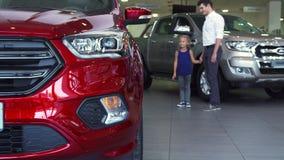 Miły ojciec z córką ogląda samochody w samochodu salonie zbiory