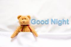 Miś kłama w białym łóżku z wiadomością & x22; Dobranoc & x22; zdjęcia royalty free