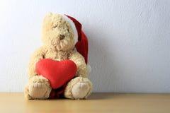 Miś z czerwonym sercem siedzi na drewnianej podłoga na biel ściany półdupkach Obrazy Stock