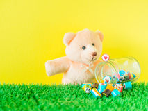 Miś zabawki spojrzenia przy czerwonym kierowym kształta cukierkiem na szklanym słoju Fotografia Stock
