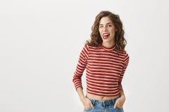 Mi accingo a vi mangio Donna sexy allegra con l'acconciatura riccia, la cima potata alla moda d'uso, attaccanti fuori lingua e Fotografie Stock