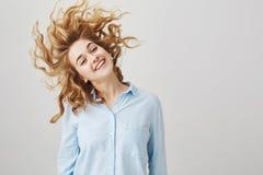 Mi corte de pelo sigue siendo lo mismo todo el día Oficinista de sexo femenino apuesto feliz con agitar del pelo rizado principal Foto de archivo