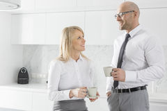 Mi couples adultes heureux d'affaires ayant le café dans la cuisine Photographie stock libre de droits