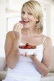 Mi femme adulte mangeant un bol de fraises photographie stock libre de droits
