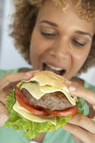 Mi femme adulte mangeant un hamburger Image libre de droits