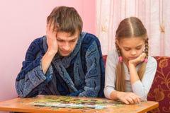 Mi hija recoge la imagen de rompecabezas, papá cansado que se sienta después Fotografía de archivo libre de regalías