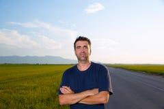 Mi homme d'âge dans la route aux prés posant les bras croisés photographie stock libre de droits