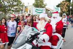 Santa Clauses on a motor scooter ride among the participants and visitors of the annual race `Cristmas Run` in Mi`ilya in Israel Royalty Free Stock Images