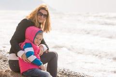 Mi madre e hija de cinco años se sientan en la playa y en el marco de torneado mirado Fotos de archivo