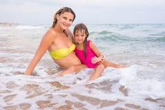 Mi madre e hija de cinco años, sentándose en el agua poco profunda en la playa Imagenes de archivo