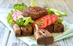 Mięso piec na grillu hamburger na drewnianej desce z warzywami Zdjęcie Stock
