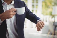 Mi section d'homme d'affaires vérifiant le temps tout en ayant le café photos libres de droits