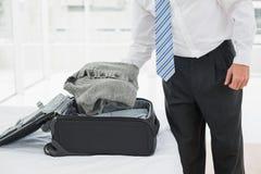 Mi section d'un homme d'affaires déballant le bagage Photo stock