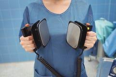 Mi section de chirurgien féminin tenant le défibrillateur Photographie stock libre de droits