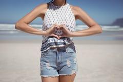 Mi section de femme faisant la forme de coeur avec des mains à la plage photographie stock libre de droits