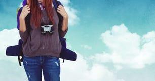 Mi section de femme se tenant avec le sac à dos et les jumelles Photos stock