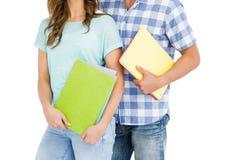 Mi section de jeunes couples tenant le livre et le dossier Photos stock