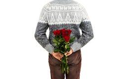 Mi section de l'homme cachant les roses rouges Photo stock